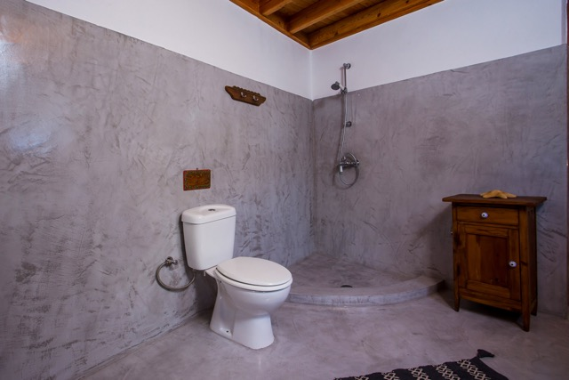 Badezimmer mit Toilette und Duschbereich