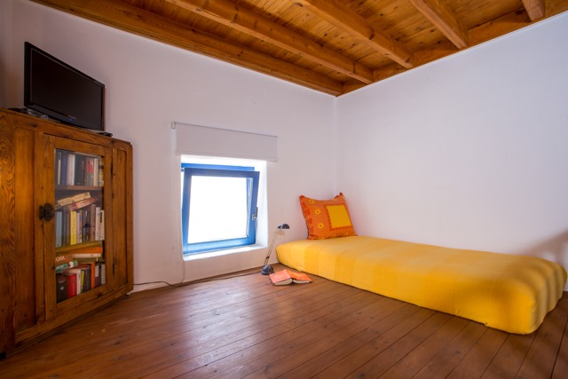Hochbett im Wohnbereich mit Bücherschrank und Fenster auf die Dorfstraße